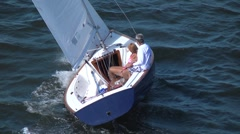 Sailboat at full sail with a man and woman aboard on a sunny day - stock footage