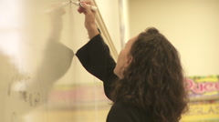 Student's teacher writes on the board Stock Footage