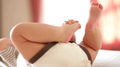 Infant grabs her foot.  Stock Footage