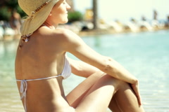 Beautiful woman in bikini and summer hat sunbathing by the water Stock Footage