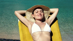 Young attractive sexy woman in summer hat sunbathing by the pool Stock Footage