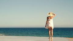 Young woman in summer hat looking out to sea Stock Footage