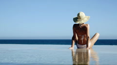 Sexy woman in summer hat and bikini sitting in infinity pool and taking sunbath Stock Footage