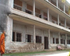Tuol Sleng, monks passing building Stock Footage