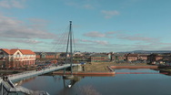Stock Video Footage of Foot bridge over urban river with modern office blocks, workers cross bridge