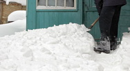 Man clearing snow off with shovel against house Stock Footage