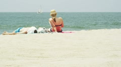 Couple sunbathing on the beach Stock Footage