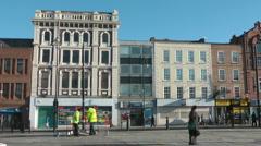 paved Georgian High Street, empty shops shuttered windows, workmen erect barrier - stock footage