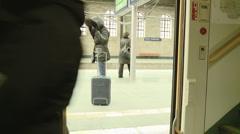woman walks away as doors of train closes - stock footage