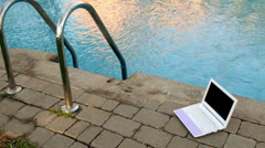 Netbook near to swimming pool Stock Footage