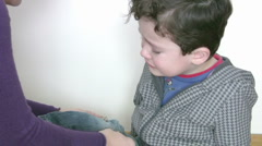 Mother putting bandage on sons leg Stock Footage