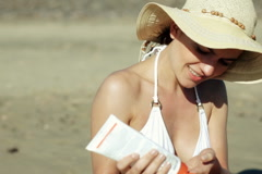 Woman on the beach applying protection lotion Stock Footage