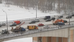 Traffic on bridge covered with white snow and snow clearing operation snowy day - stock footage