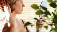 woman looking in the mirror closeup - stock footage