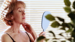 Woman looking in the mirror Stock Footage