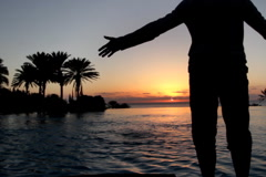 Man with arms wide open standing by the infinity pool during sunset  Stock Footage