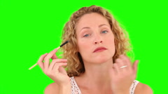 Curly blond haired female putting on make-up Stock Footage