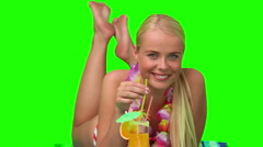 Blond female in swimsuit sipping a cocktail on the beach - stock footage