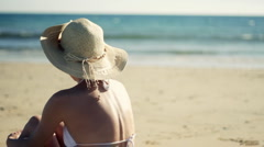 Woman in hat and bikini sitting on the beach looking out to the sea  Stock Footage