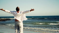 Man at the beach raising hands to the sky, freedom concept  Stock Footage