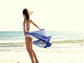Sexy woman in white bikini and sarong on the beach, slow motion Stock Footage