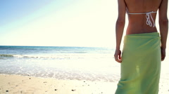 Sexy woman in sarong standing on the beach Stock Footage