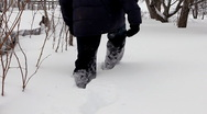 Man wades knee-deep through snow - winter garden Stock Footage