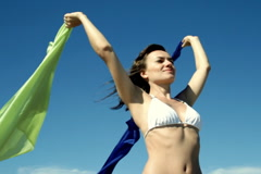 Sexy woman in white bikini holding waving sarongs against blue sky, slow motion Stock Footage