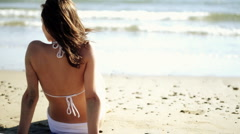 Sexy attractive woman in white bikini sitting on the beach - stock footage