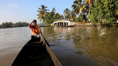 Traditional canoeing on the backwaters Kerala, nr Alleppey, India - stock footage