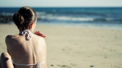 Attractive Woman on the beach applies sunscreen on her back Stock Footage