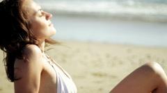 Beautiful sexy woman in white bikini taking sunbath on the beach Stock Footage