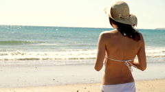 Sexy woman in summer hat and white bikini standing on the beach Stock Footage