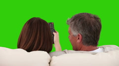 Retired couple watching tv on a sofa Stock Footage