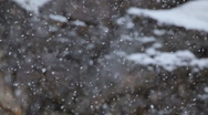 Snow falling as camera tilts down with rock cliff in background Stock Footage