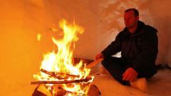 A man building a fire inside an igloo Stock Footage