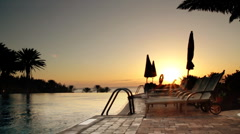 Sunbeds by the infinity pool at the sunrise - stock footage