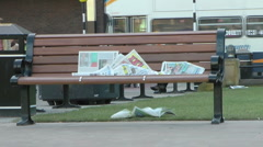 Newspaper left on an urban bench in city centre, blows in wind and litters grass Stock Footage