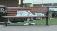 Stock Video Footage of Newspaper left on an urban bench in city centre, blows in wind and litters grass