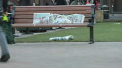 Newspaper left on a city bench blows in the wind. - stock footage