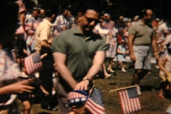 Crowd of people walking with flags, 4th of July 1962 Stock Footage