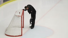 Caretaker drilling a hole in the ice - stock footage