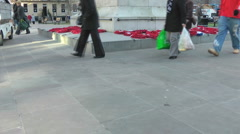 Anonymous people walk past war memorial with poppy wreaths, pan up and zoom in Stock Footage