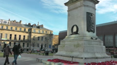 Anonymous people walk past war memorial in city square, poppy wreaths flutter Stock Footage