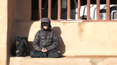 Young Man meditates on street Santa Fe, NM Stock Footage