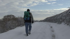 Man with rucksack walks along snow covered track. Stock Footage