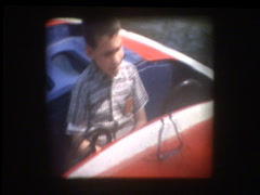 Cute little boy on boat ride at Amusement Park Stock Footage