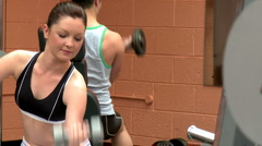 Man and woman using dumbells Stock Footage
