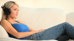 Pretty young lady listening to music on the sofa Stock Footage