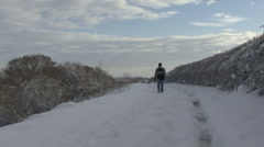 Man walks on snow covered track. - stock footage